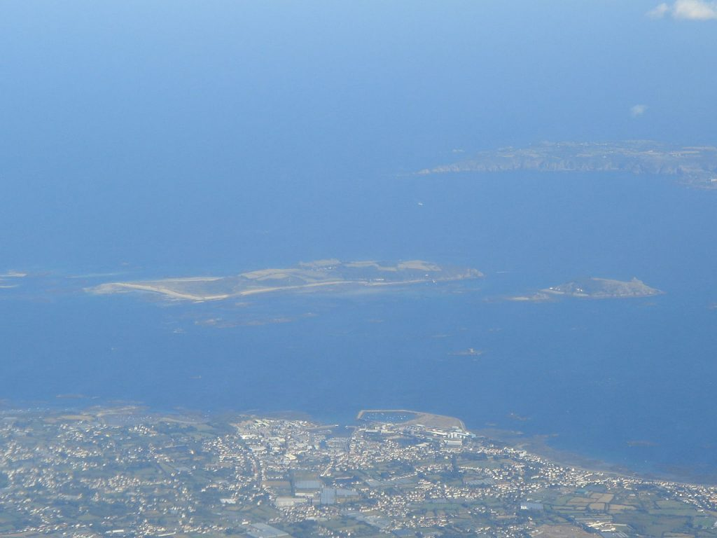 Ein Luftbild mit Herm in der Mitte, rechts davon Jethou, Sark im Hintergrund und Guernsey im Vordergrund -zwischen Guernsey und Herm verläuft Little Roussel, zwischen Herm und Sark hingegen Big Roussel